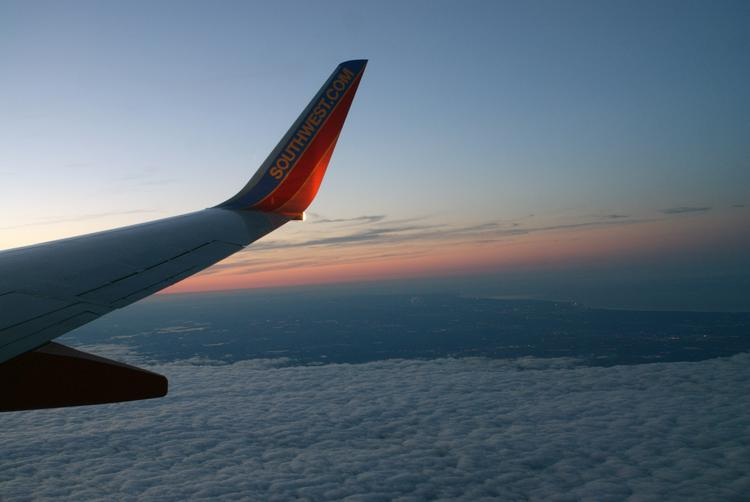 A setting sun over the distant shore of Lake Michigan; and a Southwest-emblazoned 737 winglet.