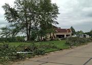 Street debris and a damaged house in the Camelot subdivision.