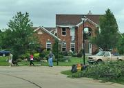 A damaged home in the Camelot subdivision. Construction and storm emergency vehicles on scene.