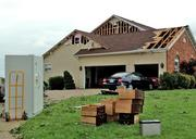 The same house with damage to the side and roof.