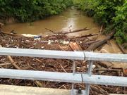A creek with debris on Highway K in O'Fallon, Mo.