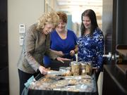 Rhoda Olsen buys baked goods from Terri Stephenson (left) and her sister Dottie Werner during Great Deeds week in the office to raise money for Gillette Children's Hospital.