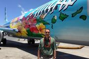 Alaska Airlines President and CEO Brad Tilden poses next to a Boeing 737-800 painted with the winning design by Kaiser High School Student Aaron Nee after the plane landed at Honolulu International Airport.