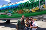 Alaska Airlines President and CEO Brad Tilden and Kaiser High School student Aaron Nee pose with Wade Raboy, an Alaska Airlines pilot from Maui in front of a Boeing 737-800 painted with Nee's winning design after the plane landed at Honolulu International Airport.