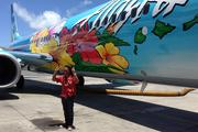 "Hawaiian entertainer Henry Kapono, one of the judges of Alaska Airlines' ""Paint the Plane"" contest, poses in front of student Aaron Nee's winning design."