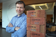 Jama Software CEO Eric Winquist stands with a pillar of bricks, each representing a $100,000 client. The company is expanding its headquarters in Portland and expects a big year in 2014.