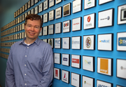 Jama Software CEO Eric Winquist pauses in front of a wall highlighting the company's clients.
