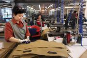 From left, Nhi Ly and Phong Phu work on bags at Filson in the company's new headquarters building on First Avenue. The lobby and the manufacturing floor,  where Filson's popular bags are made, are separated by a wall of glass.  The Filson's headquarters building also houses offices and a showroom.