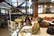 Phuong Phan (front) sews a computer bag at Filson in the company's new headquarters building on First Avenue. The lobby and the manufacturing floor,  where Filson's popular bags are made, are separated by a wall of glass.  The Filson's headquarters building also houses offices and a showroom.