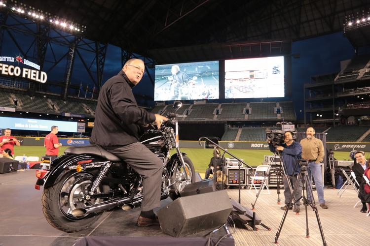 A crowd of more than 900 people roared their approval when former Seahawks Coach Mike Holmgren, one of the chairs of Medical Teams International's Field of Dreams auction at Safeco Field, rode up on a Harley motorcycle.