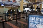 A Transportation Security Administration officer stands at the end of an empty line at Reagan National Airport.
