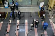 A traveler walks into an empty Transportation Security Administration line at Reagan National Airport.