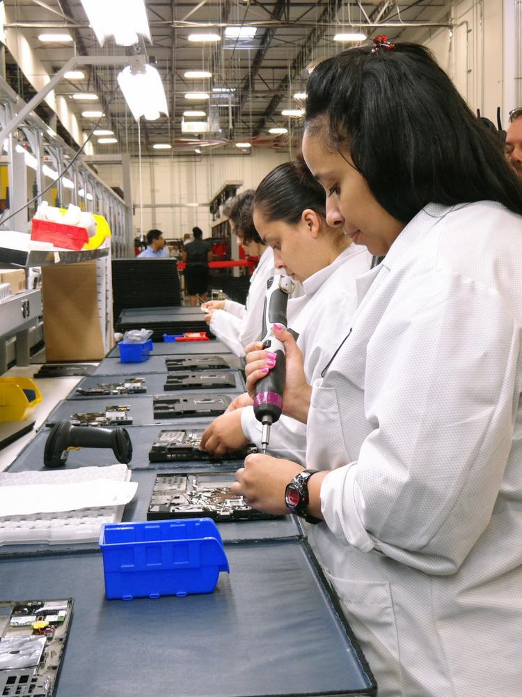 Assembly line employees work on new computers at the newly opened Lenovo manufacturing facility in Whitsett, N.C.