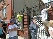 Neighbors look on as first responders help remove people from the rubble of a building collapse in Philadelphia.