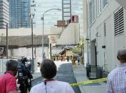 The news media looks on as first responders help remove people from the rubble of a building collapse in Philadelphia.