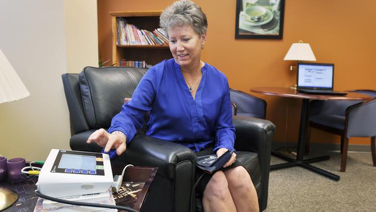 Karen Kozyra, RN at Centura Home Health, demonstrates how a telehealth patient answers questions and inputs vitals for transmission to a nurse.