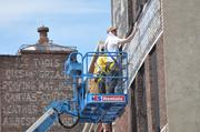 Painters Michael Conlin and Frank Smith restore ghost signs in downtown Albany. One to three more buildings downtown will be added to the list, pending approval from landlords.