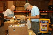 Rob Foote and Tony DeFilippo, volunteer food sorters, in the food bank warehouse at Meals on Wheels Plus of Manatee Inc.