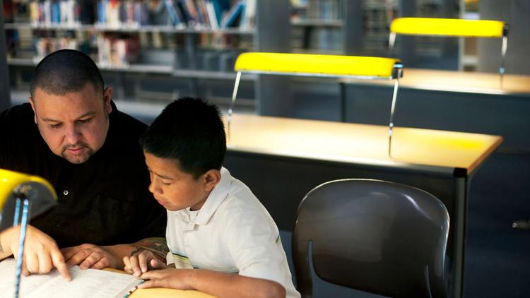 A Big Brother helps a Little Brother out at the library.
