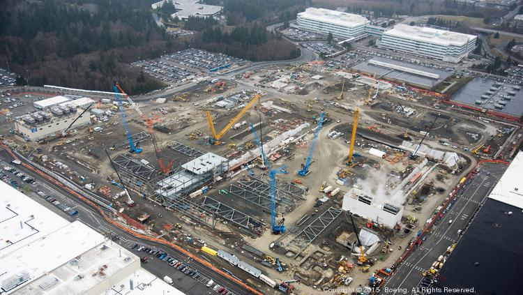 In the foreground, you can see where crews have begun erecting steel walls on the west edge of the Boeing 777X site. Other trusses are laid out, positioned for placement by the many cranes on the site. Boeing's large Everett office buildings can be seen in the background.