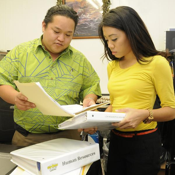 Nathan Okinaka, director of operations of So Ono Food Products, talks with HR and administrative assistant Sara-Malia Scott. The company has chosen to keep its HR functions in-house despite higher costs.