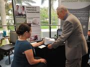 Shaneka Rose of Nipro Diagnostics takes an antioxidant test from Lawrence Cazan Cassini of MD Solutions.