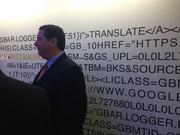 """City Councilman Bill Peduto standing in front of a wall of code at Google's Pittsburgh office. The walls of this corridor are covered in code. When you type in """"Google Pittsburgh"""" to Google this is the code used to return your results."""