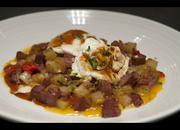 The Red Roost Tavern serves corned beef hash with local ingredients. A poached egg and spicy demi sauce enhance the flavor.
