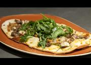 On the menu is flatbread made in-house with chicken served on a bed of arugula.