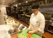 Line cook Ladena Gough cuts produce in the kitchen. The open concept at Red Roost Tavern allows guests to see into the kitchen as food is being prepared.