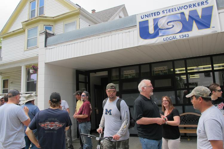 United Steelworkers Local 1343 members discuss the Caterpillar contract outside the union hall in South Milwaukee.