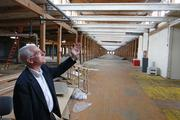 Eakes shows off the natural light that flows in from the former textile mill's tall windows. The first phase of renovation will involve restoring about 340 12-foot windows, which must be made weather-tight and sustainable before the buildings can reach shell status.
