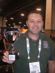 """Douglas Holmes, the plant manager at Oklahoma City Water Utilities Trust's Hefner Water Treatment Plant, hoists the winner's trophy for hoisted the winner's trophy for the """"Best of the Best"""" tap water taste test competition June 11 at the American Water Works Association's 13th annual convention, held at the Colorado Convention Center in Denver."""