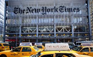Taxi cabs rush past The New York Times Co. headquarters.