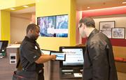 A Wells Fargo banker, left, assists a customer at the bank's first neighborhood store in Washington, D.C.
