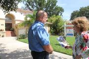 Brad Monroe, local real estate agent with Prudential Tropical Realty and former president of the Greater Tampa Association of Realtors, speaking with an interested home buyer at a Tampa listing.