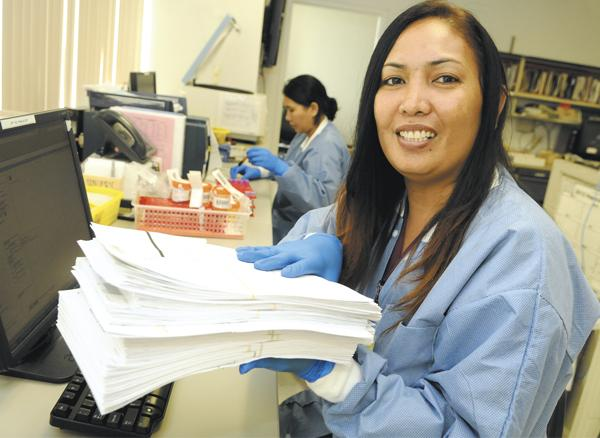 Brandy Westlake, a lab assistant supervisor for Clinical Laboratories of Hawaii, holds a weekend's worth of requisitions that Profitability of Hawaii will scan into a digital format. Going digital is credited with increasing work productivity.