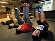 """Red Russak (center) and his Apptentive co-workers Ezra Siegel (left) and Robi Ganguly (2nd left)  do an """"8 Minute Abs"""" video workout during their daily meeting with Ahmed Elbortoukaly, who is co-founder of Snazz.it, a startup."""
