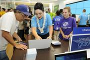 Noelle Neverdon, manager at the new Microsoft Store at Ala Moana Center, center, assists a customer.