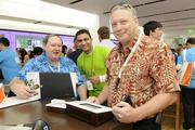 Daniel Woods, right, enterprise architect for High Performance Systems, purchases a Surface Windows RT with a $100 discount coupon as Ed Raney, of High Performance Systems, left, and Sohel Bobat, technical advisor for Microsoft, center, look on at the new Microsoft Store at Ala Moana Center.
