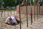 The final obstacle of the Gladiator Dash required participants to crawl under wires through sand.