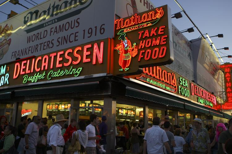 People walk past the original Nathan's Famous hot dog stand on Coney Island.