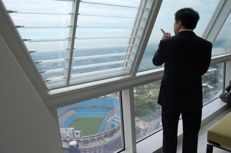 Baoding, China Vice-Mayor Zhou Xingshi, pictured here, takes in a view of Bank of America stadium from the top of the Duke Energy Center in uptown. Zhou led the delegation of officials and business executives from Baoding, China on June 17 and 18 to learn more about Charlotte's growing energy cluster and the city's management of government functions including sustainability.