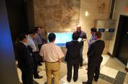 Packard Place co-founder Dan Roselli shows a delegations of officials and business executives from Baoding, China a kiosk that tracks energy use. The group toured Charlotte on June 17 and 18 to learn more about its growing energy cluster and the city's management of government functions including sustainability.