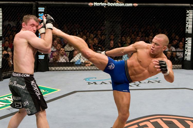 """Ultimate Fighting Championship fighter Georges """"Rush"""" St-Pierre, right, kicks an opponent in the Ultimate Fighting octagon."""
