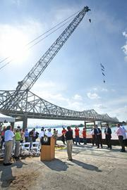 The crowd watched as a crane hoisted the American, Kentucky and Indiana flags over the construction site.