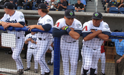 A handful of Hops players watch the field as play begins on opening day.