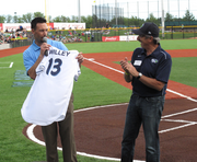 Hillsboro Hops general manager K.L. Wombacher (left) presents Hillsboro mayor Jerry Willey with his own jersey before Monday evening's game.
