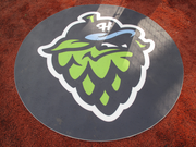 The Hops logo is proudly displayed on the on-deck circle at Hillsboro Stadium.