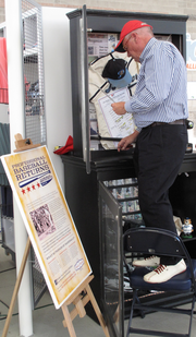 A man puts the finishing touches on a history of Portland-area baseball exhibit, on display at Hillsboro Stadium.